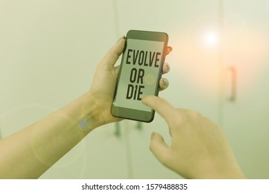 Word writing text Evolve Or Die. Business concept for Necessity of change grow adapt to continue living Survival woman using smartphone office supplies technological devices inside home.