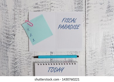 Word writing text Fiscal Paradise. Business concept for The waste of public money is a great concern topic Open squared spiral notepad clip note highlighter lying old wooden background.