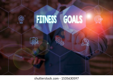 Word writing text Fitness Goals. Business concept for Loose fat Build muscle Getting stronger Conditioning Male human wear formal work suit presenting presentation using smart device.