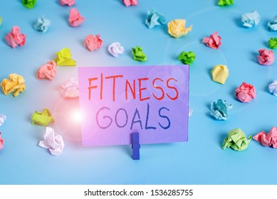Word writing text Fitness Goals. Business concept for Loose fat Build muscle Getting stronger Conditioning Colored crumpled papers empty reminder blue floor background clothespin.