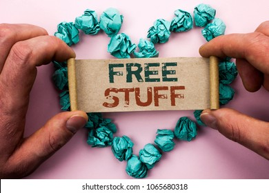 Word writing text Free Stuff. Business concept for Complementary Free of Cost Chargeless Gratis Costless Unpaid written on Cardboard Paper Holding by man plain background on Heart Paper Balls.