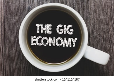 Word writing text The Gig Economy. Business concept for Market of Short-term contracts freelance work temporary Black coffee with coffee mug floating texts on gray black wooden desk.