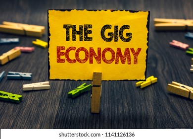 Word writing text The Gig Economy. Business concept for Market of Short-term contracts freelance work temporary Blacky wooden desk laid paper clip randomly one hold yellow board with text.