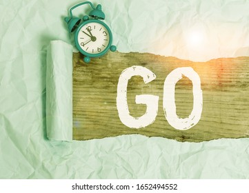 Word writing text Go. Business concept for to move or travel somewhere in order to do something Leave or depart Alarm clock and torn cardboard placed above a wooden classic table backdrop.