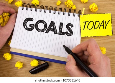 Word writing text Goals. Business concept for Desired Achievements Targets What you want to accomplish in the future written by Man on Notepad holding  Marker on wooden background Today Paper Balls