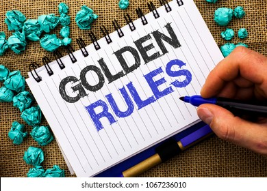 Word writing text Golden Rules. Business concept for Regulation Principles Core Purpose Plan Norm Policy Statement written by Man Holding Marker Notebook Book the jute background.