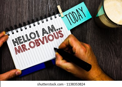 Word writing text Hello I Am.. Mr.Obvious. Business concept for introducing yourself as pouplar or famous person Man holding marker notebook clothespin hold reminder coffee cup wood table.