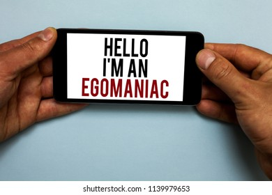 Word writing text Hello I am An Egomaniac. Business concept for Selfish Egocentric Narcissist Self-centered Ego Human hand hold smartphone with red and black letters on shadow blue floor.