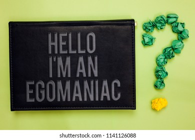 Word writing text Hello I am An Egomaniac. Business concept for Selfish Egocentric Narcissist Self-centered Ego Green back black plank with text green paper lob form question mark.