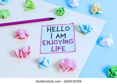 Word writing text Hello I Am Enjoying Life. Business concept for Happy relaxed lifestyle Enjoy simple things Colored crumpled papers empty reminder blue yellow background clothespin.