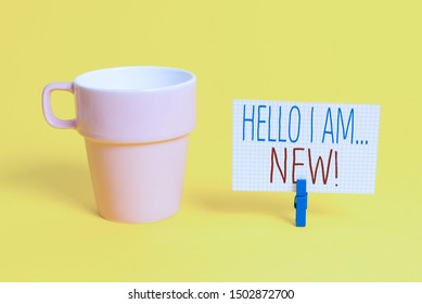 Word writing text Hello I Am New. Business concept for used as greeting or to begin telephone conversation Cup empty paper blue clothespin rectangle shaped reminder yellow office.