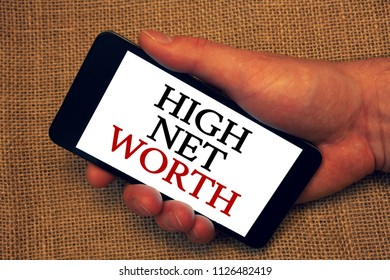 Word writing text High Net Worth. Business concept for having high-value Something expensive A-class company Owner hold holding smartphone white screen message application intention.
