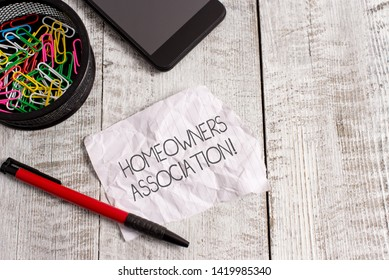 Word writing text Homeowners Association. Business concept for Organization with fee for upkeeps of Gated Community Wrinkle paper and notebook plus stationary placed above wooden background.