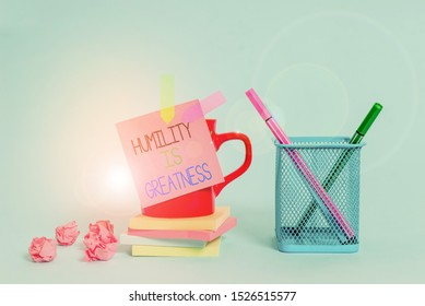 Word writing text Humility Is Greatness. Business concept for being Humble is a Virtue not to Feel overly Superior Cup pens holder note banners stacked pads paper balls pastel background.