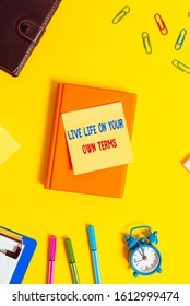 Word writing text Live Life On Your Own Terms. Business concept for Give yourself guidelines for a good living Flat lay above table with copy space paper clips clock and pencils.