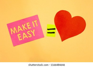 Word writing text Make It Easy. Business concept for Smart approach Effortless Free from worries or difficulties Pink piece paper reminder equal sign red heart sending romantic feelings.
