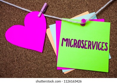 Word writing text Microservices. Business concept for Software development technique Decomposing an application Heart thread sticky small cliped string thumb pin dark rough background.