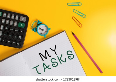 Word writing text My Tasks. Business concept for assigned piece of work often to be finished within a certain time Open striped notebook calculator clips pencil alarm clock color background.