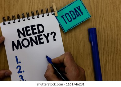 Word writing text Need Money question. Business concept for asking someone if he needs cash or bouns Get loan Man holding marker notebook clothespin reminder wooden table cup coffee.