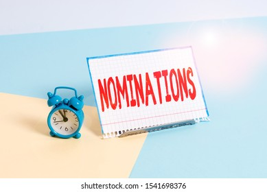 Word writing text Nominations. Business concept for action of nominating or state being nominated for prize Mini size alarm clock beside a Paper sheet placed tilted on pastel backdrop.