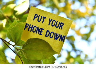 Word writing text Put Your Phone Down. Business concept for end telephone connection saying goodbye caller Piece of square paper use to give notation on tree leaf under sunny day.