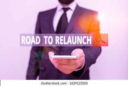 Word writing text Road To Relaunch. Business concept for In the way to launch again Fresh new start Beginning Male human wear formal work suit hold smart hi tech smartphone use one hand.