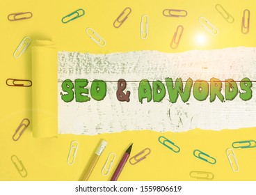 Word writing text Seo And Adwords. Business concept for Pay per click Digital marketing Google Adsense Stationary and torn cardboard placed above a wooden classic table backdrop.