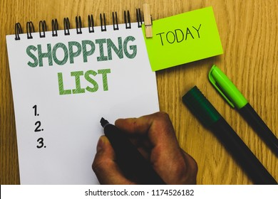 Word writing text Shopping List. Business concept for Discipline approach to shopping Basic Items to Buy Man holding marker notebook clothespin reminder wooden table cup coffee.