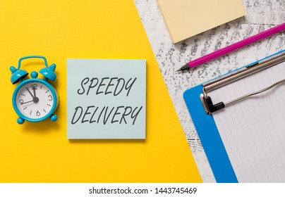 Word writing text Speedy Delivery. Business concept for provide products in fast way or same day shipping overseas Notepads clipboard colored paper sheet marker alarm clock wooden background.