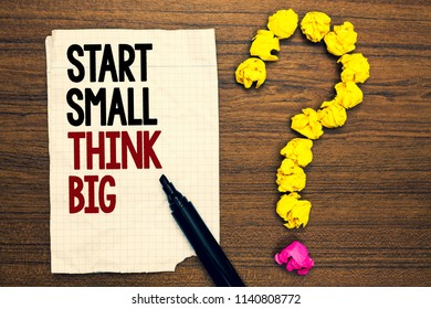 Word writing text Start Small Think Big. Business concept for Initiate with few things have something great in mind Written torn page touch black pen yellow paper lob form question on woody deck.