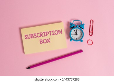 Word writing text Subscription Box. Business concept for button if you clicked on will get news or videos about site Colorful blank notepad marker retro alarm clock clip colored background.