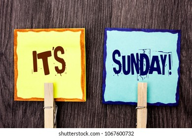 Word writing text It's Sunday Call. Business concept for Relax Enjoy Holiday Weekend Vacation Rest Day Free Relaxing written on Sticky Note Papers Holding with Wooden Clip on the wooden background.