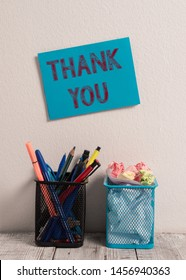 Word writing text Thank You. Business concept for a polite expression used when acknowledging a gift or service Blue Sticky Card on Wall Two Pencil Pots Pens Pencils Markers Waste Paper.