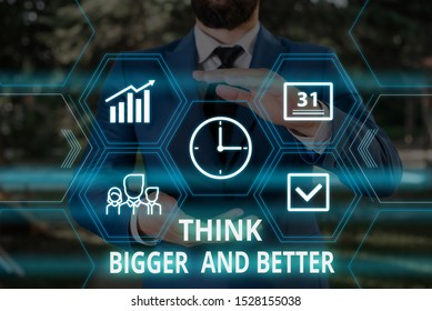 Word writing text Think Bigger And Better. Business concept for no Limits be Open minded Positivity Big Picture Male human wear formal work suit presenting presentation using smart device.