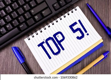 Word writing text Top 5 Motivational Call. Business concept for The best ones Winners Most Popular Bestsellers written on Notepad on wooden grey background Pens and Black Keyboard next to it.