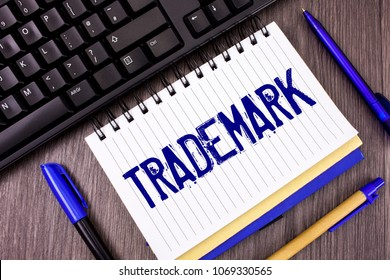 Word writing text Trademark. Business concept for Legally registered Copyright Intellectual Property Protection written on Notepad on wooden grey background Pens and Black Keyboard next to it.
