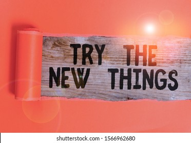 Word writing text Try The New Things. Business concept for Breaks up Life Routine Learn some Innovative Skills Cardboard which is torn in the middle placed above a wooden classic table.