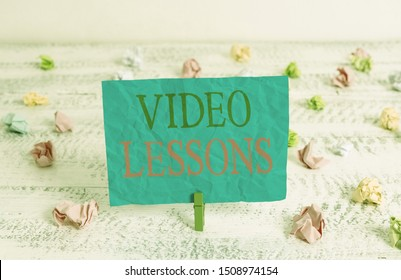 Word writing text Video Lessons. Business concept for Online Education material for a topic Viewing and learning Green clothespin white wood background colored paper reminder office supply.