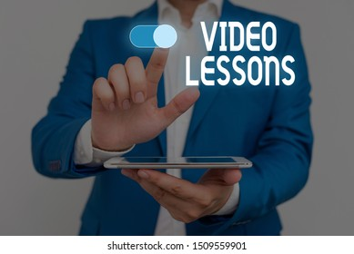Word writing text Video Lessons. Business concept for Online Education material for a topic Viewing and learning Male human wear formal work suit presenting presentation using smart device.