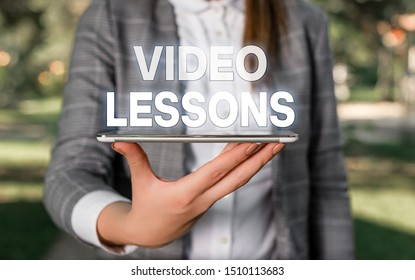 Word writing text Video Lessons. Business concept for Online Education material for a topic Viewing and learning Outdoor scene with business woman holds lap top with touch screen.