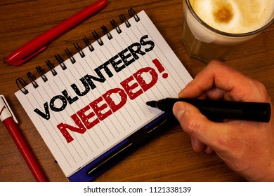 Word writing text Volunteers Needed Motivational Call. Business concept for Social Community Charity Volunteerism Hand grasp black marker wooden desk red pen notepad expos texts coffee.