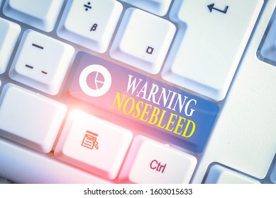 Word writing text Warning Nosebleed. Business concept for caution on bleeding from the blood vessels in the nose White pc keyboard with empty note paper above white background key copy space.