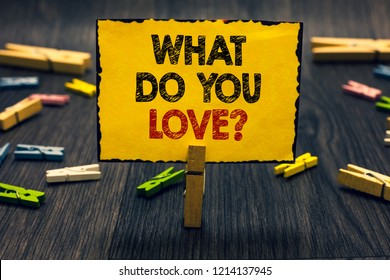 Word writing text What Do You Love question. Business concept for Enjoyable things passion for something inspiration Blacky wooden desk laid paper clip randomly one hold yellow board with text.