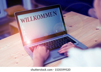 Word writing text Willkommen. Business concept for welcoming showing event or your home something to that effect woman laptop computer smartphone mug office supplies technological devices.