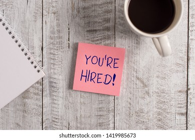 Word writing text You Re Hired. Business concept for Used by huanalysis resources indicate employee that he is got job Stationary placed next to a cup of black coffee above the wooden table.