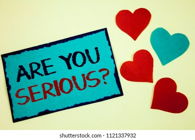 Word writing text Are You Serious Question. Business concept for Have to be kidding me Disbelief Is it for real Turquoise note ideas black red letters words hearts frame beige background.