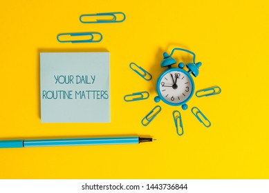 Word writing text Your Daily Routine Matters. Business concept for practice of regularly doing things in fixed order Metal alarm clock wakeup clips ballpoint notepad colored background.