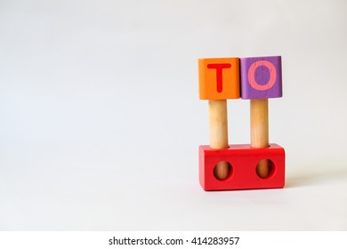TO word written on wood blocks, white background with copyspace