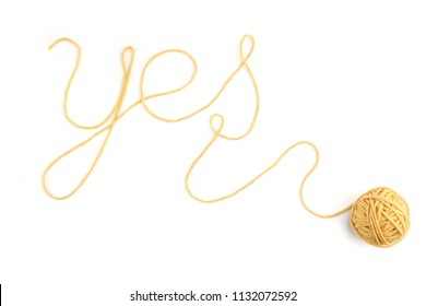 Word yes made of yellow thread and thread ball isolated on white background. Cotton thread ball with word yes.