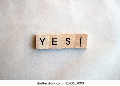 The word Yes! written in black letters on wooden blocks. Message spells Yes on white background. Business, motivation and education concept